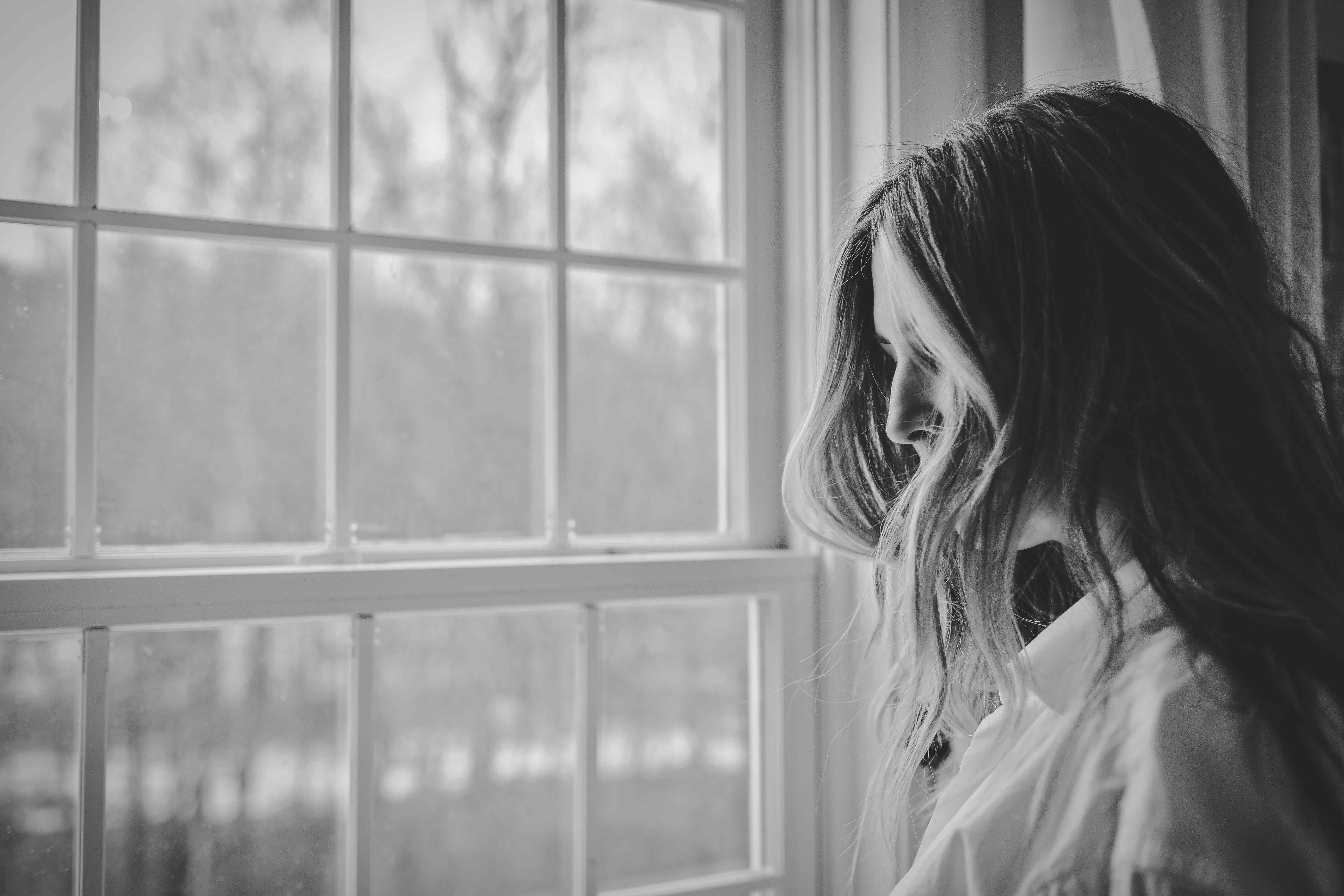 Photo of woman looking out of a window, Photo by Danielle MacInnes on Unsplash